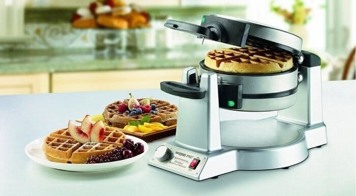 A Belgian waffle maker cooking a waffle with two already prepared waffles plated next to it