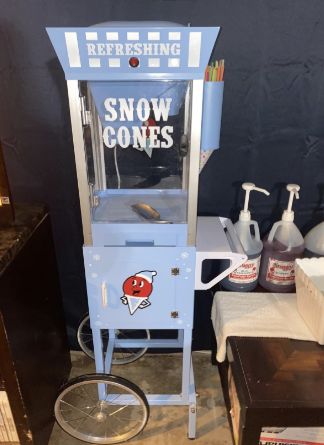 a light blue, tall, vintage-looking snow cone machine with a cute snow cone character on it and two wheels