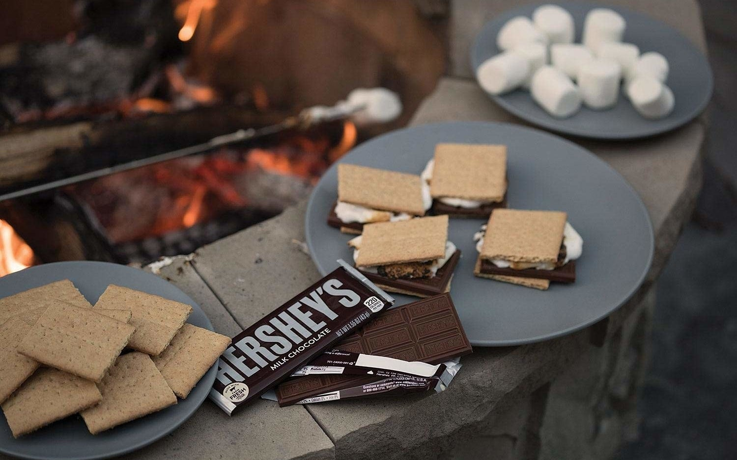 an open hershey's chocolate bar next to a plate of s'mores nearby a fire