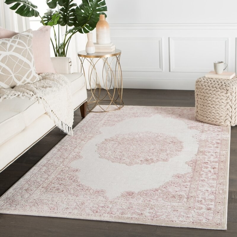 An area rug staged in a living room with soft vintage floral detailing