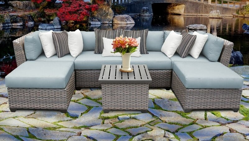A large cushioned wicker outdoor seating couch in seven pieces that can be arranged in different ways, including a square table in the middle of them