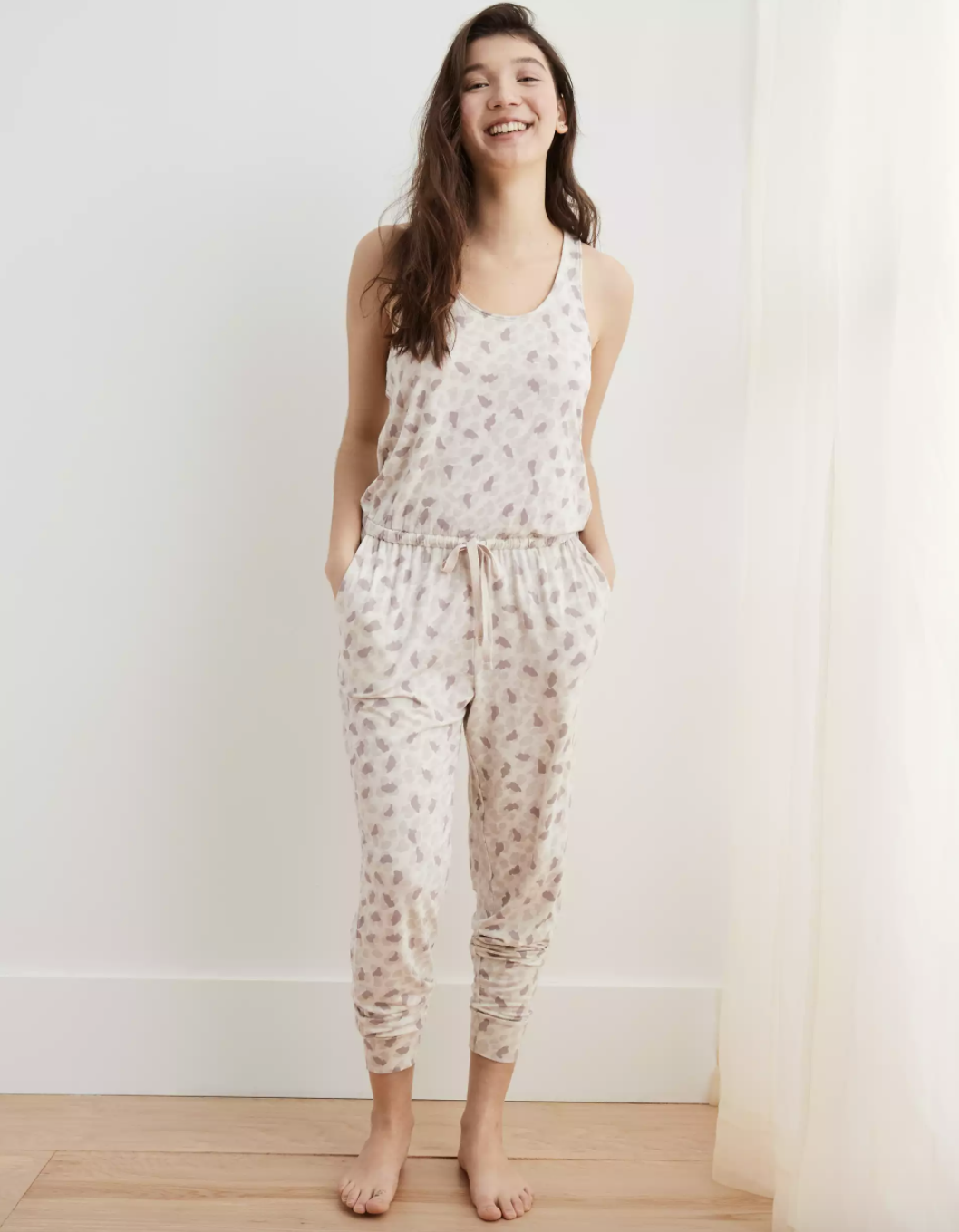 A model standing in a white bedroom setting wearing the comfy jumpsuit