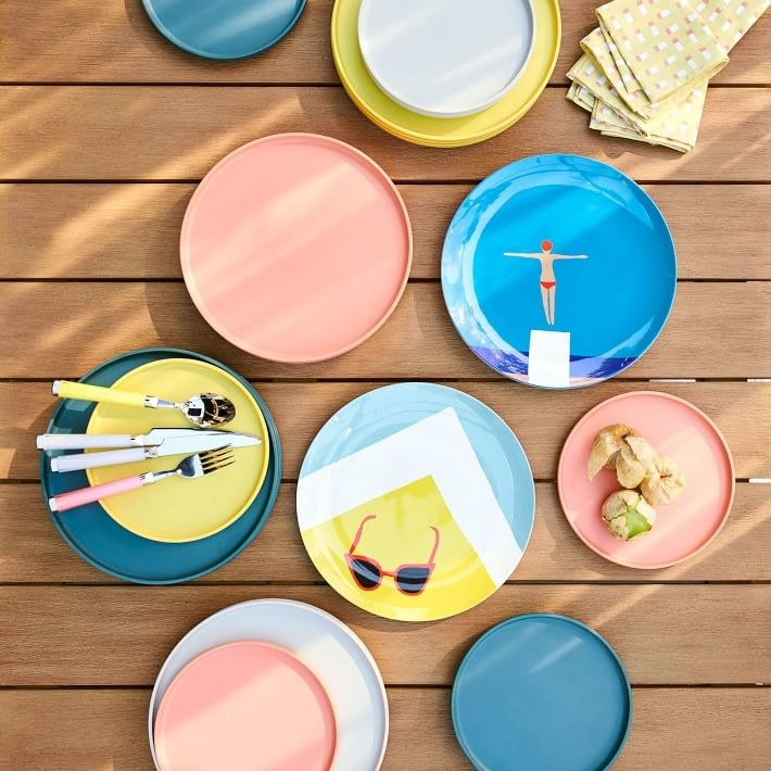 a wooden table filled with brightly colored melamine outdoor plates one has sunglasses on top of a light blue, white, and yellow triangular design while another is blue and made to look like someone is diving off a diving board into water