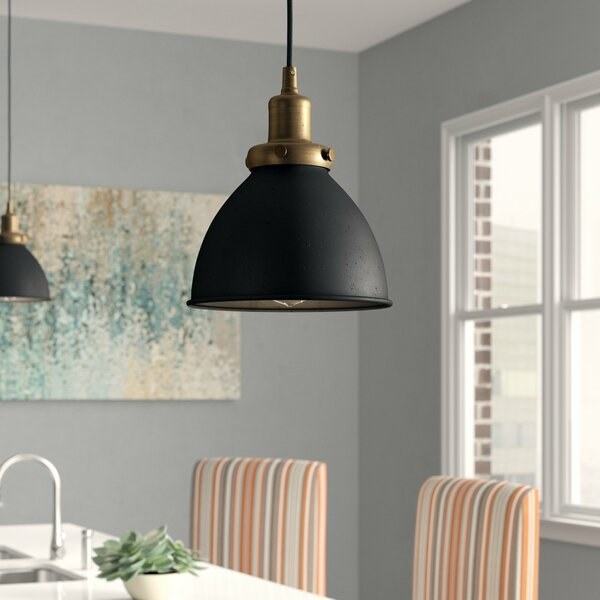 kitchen scene with focus on lighting pendant hanging from ceiling with black bell-shaped body and brass accents that give it in an industrial style