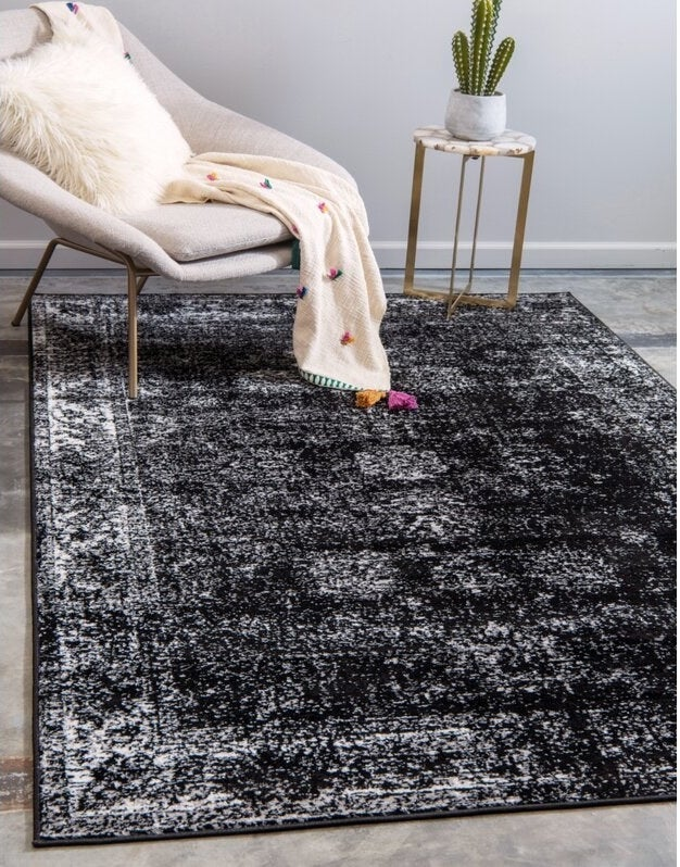 A large black rug with white and gray distressed detailing