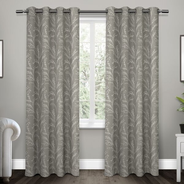 floral gray and silver pattern curtains hanging on a window and brushing the ground. Grommet tops of curtains for sliding onto a curtain rod