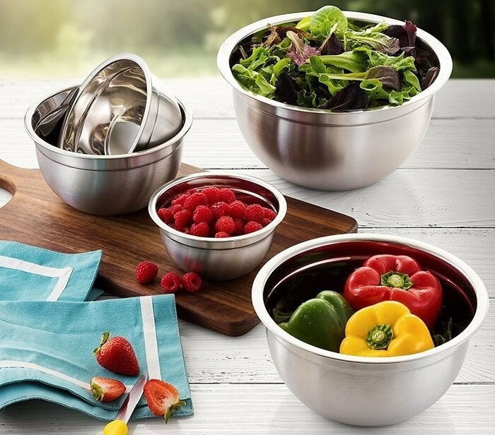A set of five stainless steel mixing bowls of varying sizes holding produce
