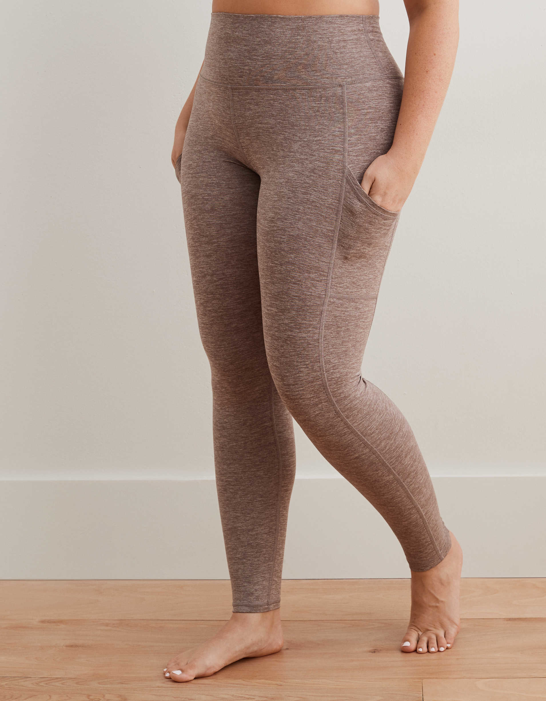 model in purple and grey heathered high waisted leggings with pockets on the side of the thighs