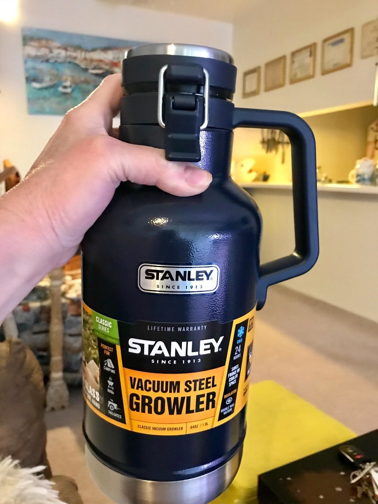 A hand holding a dark blue Stanley vacuum steel growler