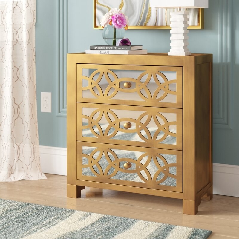 A subtly shiny gold cabinet, approximately the height of a nightstand, with three drawers with art deco-esque designs and reflective mirror panels on them