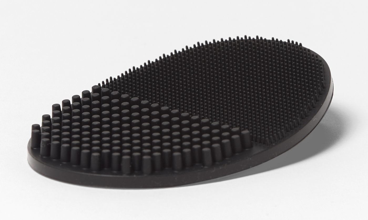 A close-up of a black oval-shaped pad with thick silicone bristles on one side and thinner silicone bristles on the other side