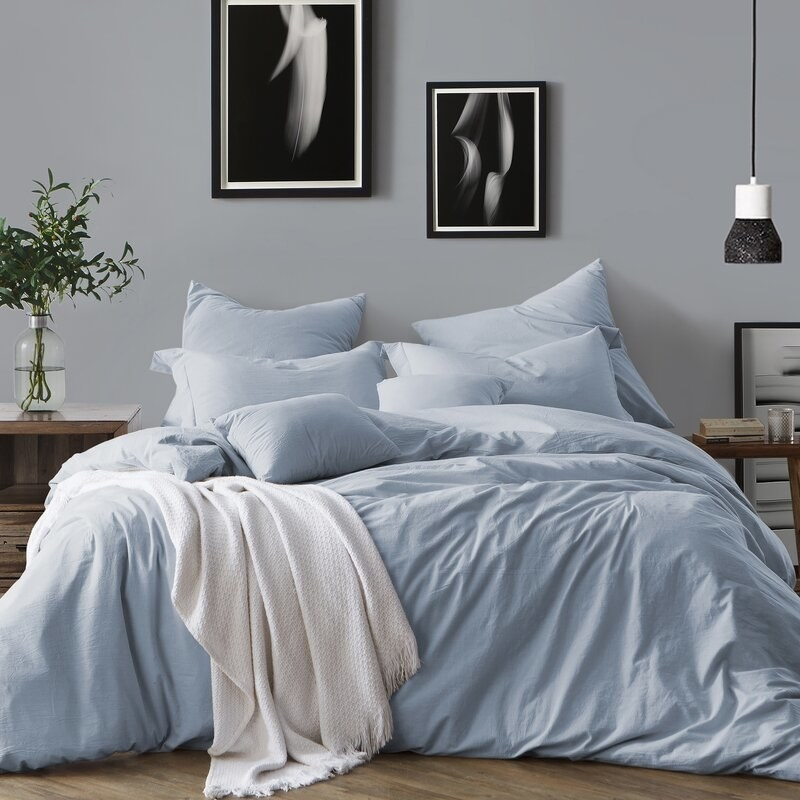 A bed with a very fluffy, long duvet with a blue duvet cover on it, displayed with match blue pillowcases