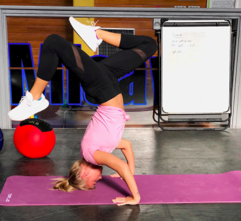 A woman does a headstand on the TOPLUS Yoga mat
