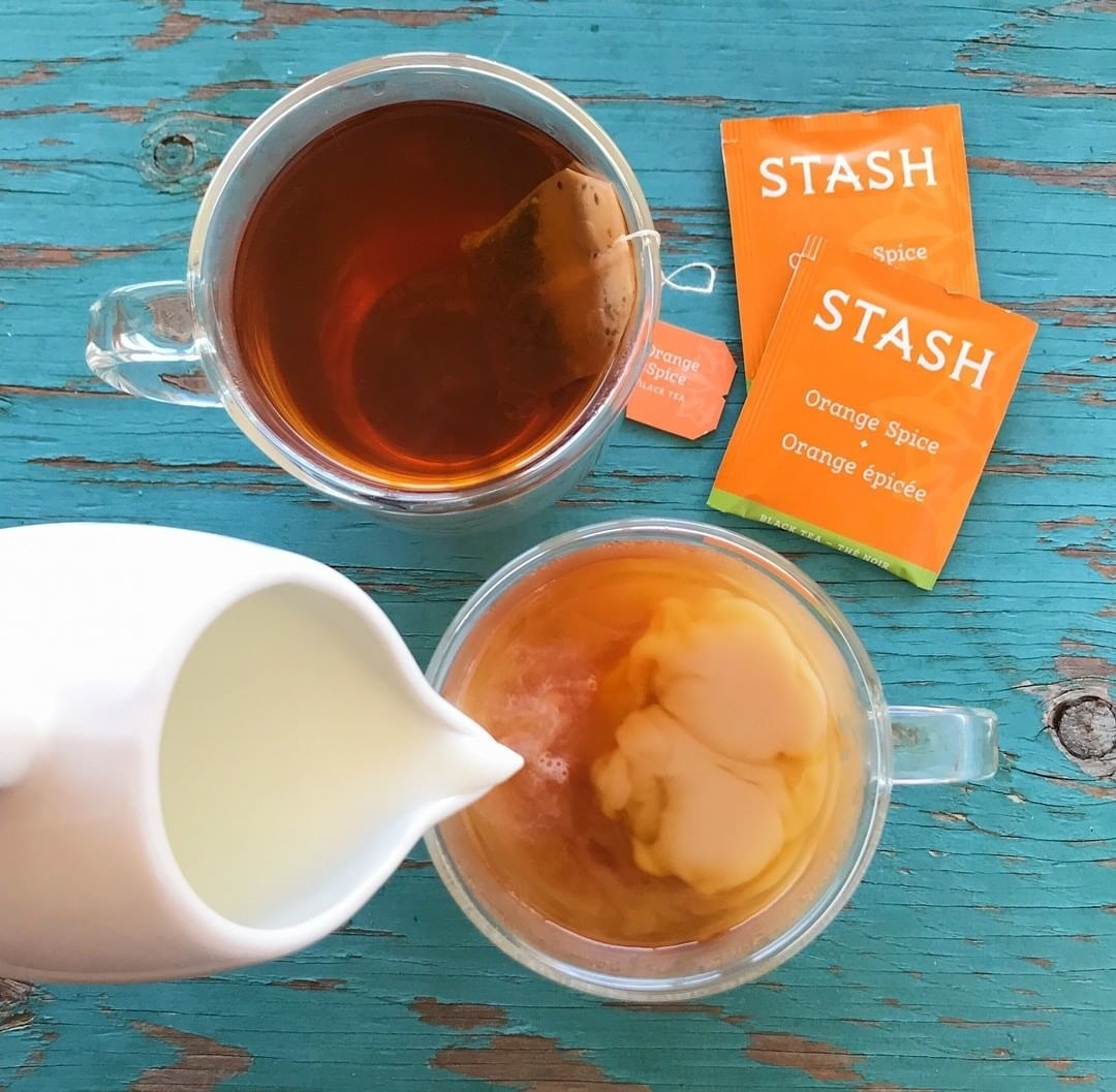two orange spice stash tea bags next to two cups of tea, one has milk being added to it