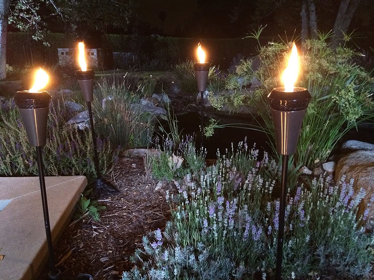 four gun metal tiki torches in a backyard at night
