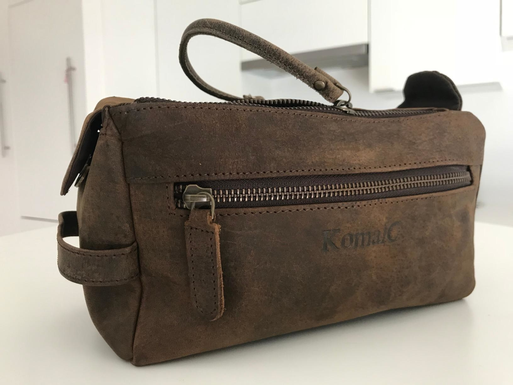 A brown leather dopp kit with two closed zippers