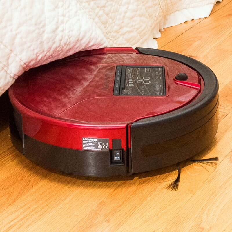 The disc-shaped robot cleaner working on a hardwood floor