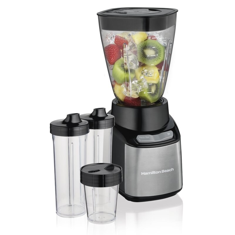 A transparent blender full of fruit and ice with several portable cups included