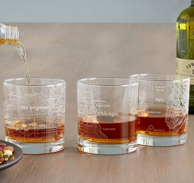 Three whiskey-size glasses etched with maps of LA, Chicago, and NYC