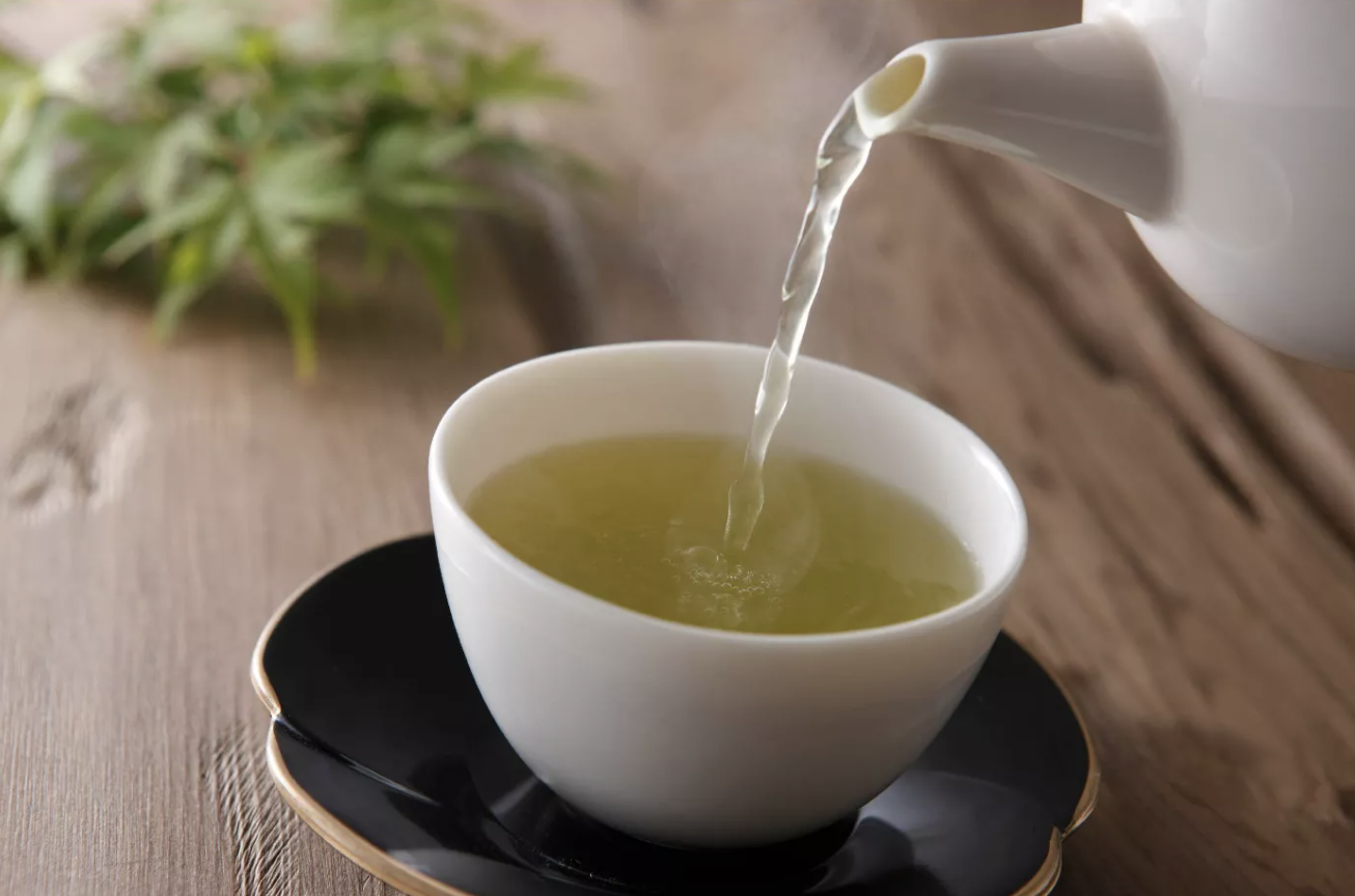 a tea cup with green tea being poured into it from a tea pot
