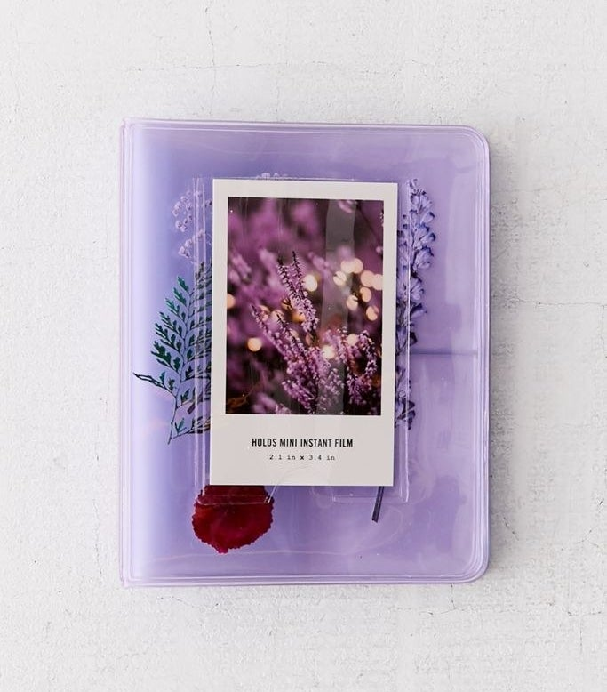 a purple transparent photobook with dried flowers encased inside