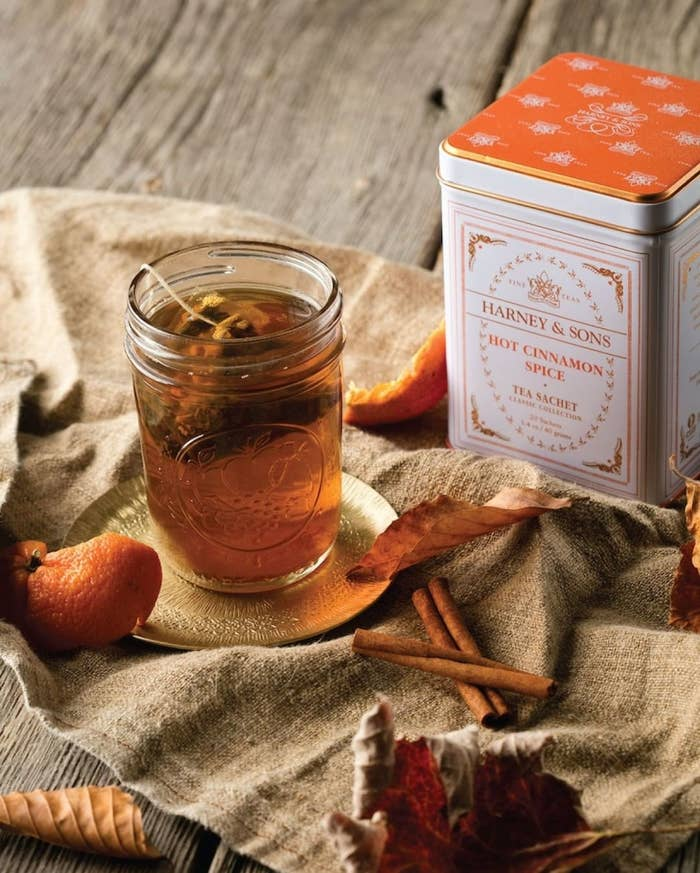 "a cozy fall tea in a mason jar next to a decorative tin container that reads ""harney and sons hot cinnamon spice tea"""
