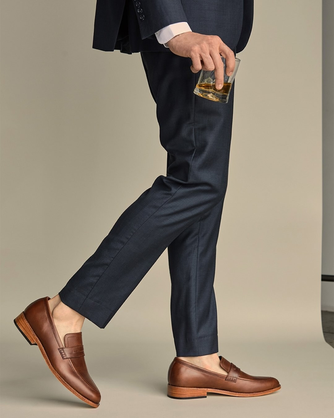 A model wearing the loafers with no-show socks and dress pants