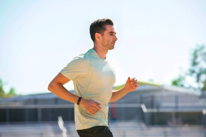 A man jogs outside while wearing the Fitbit