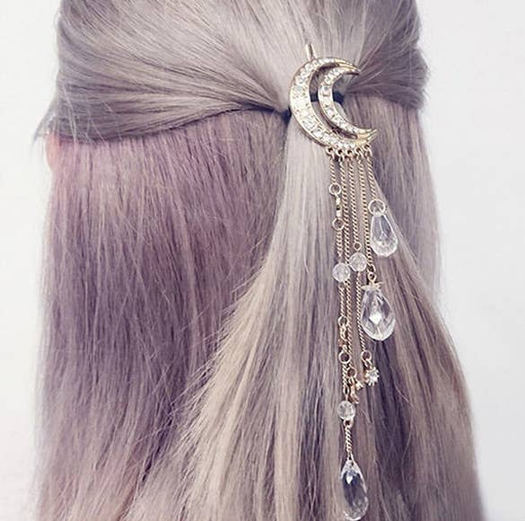 The back of head wearing a rhinestone-covered moon hair clip with five chains with hanging crystal-like droplets