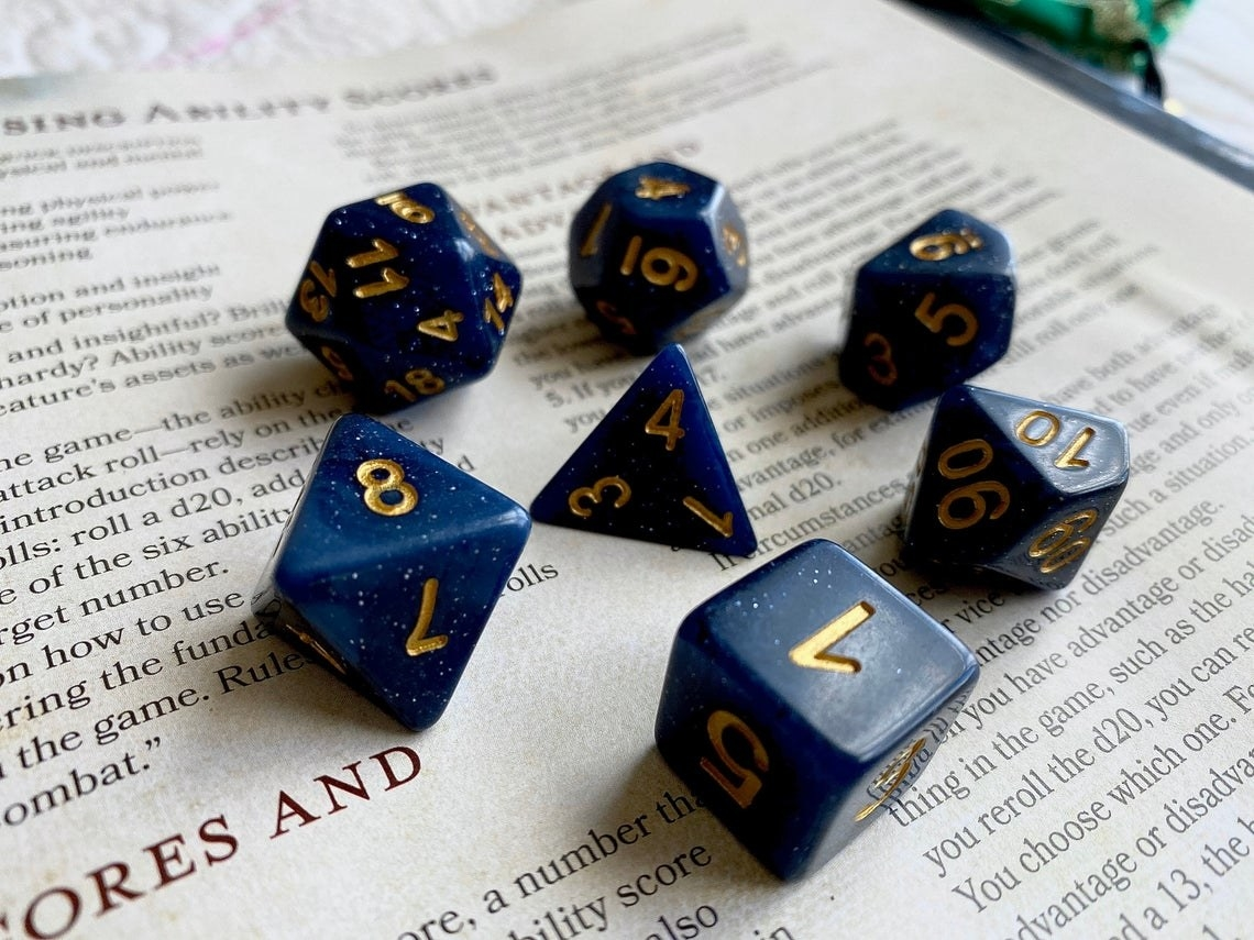 blue dice with gold numbers on book page