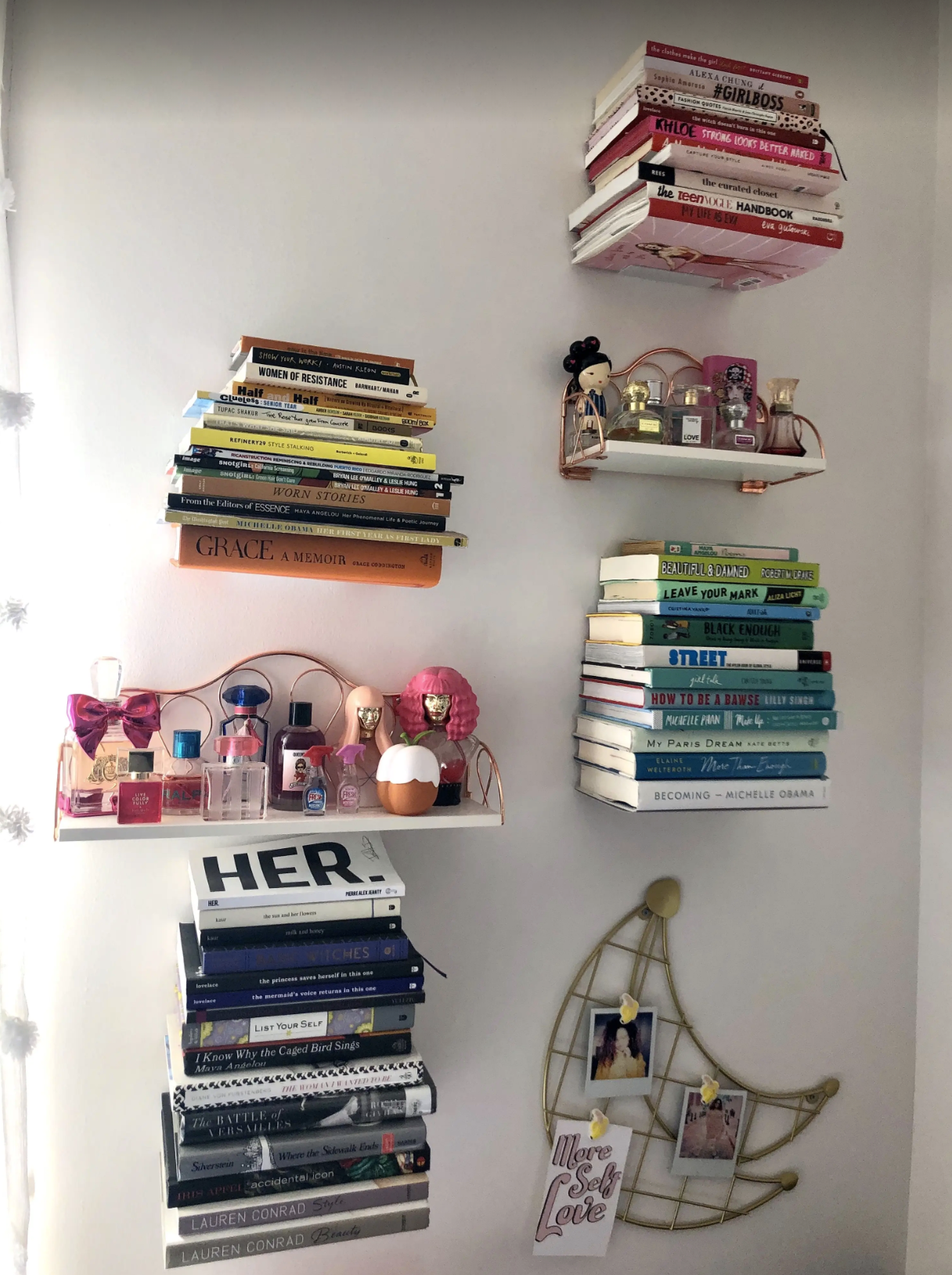 Several floating bookshelves with books stacked by color on BuzzFeed editor Kayla Boyd's wall