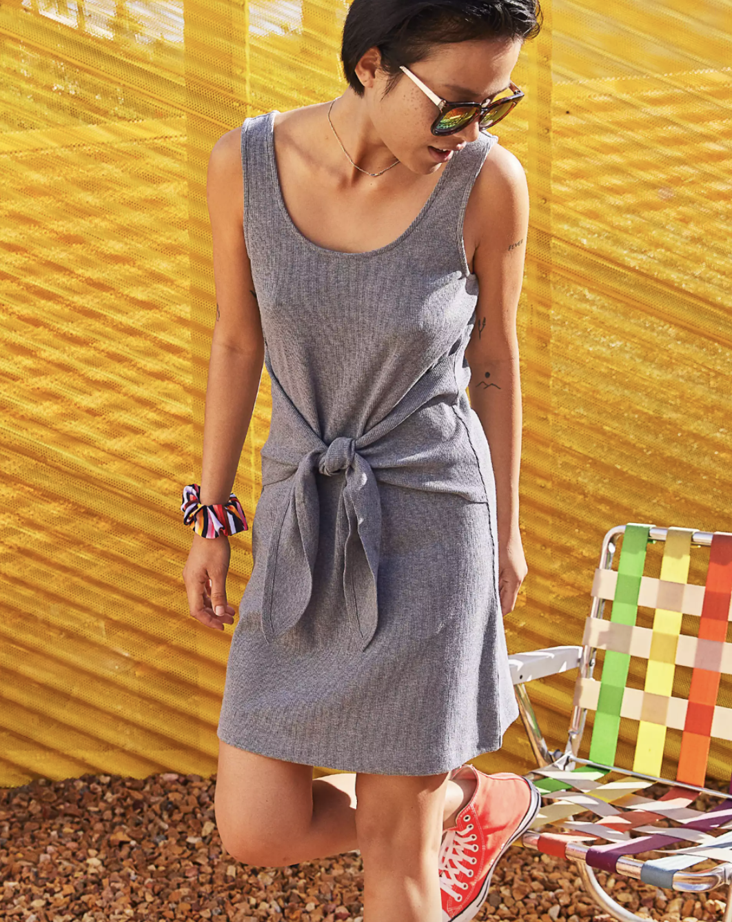 A model wearing the knit tie dress with sneakers and sunglasses