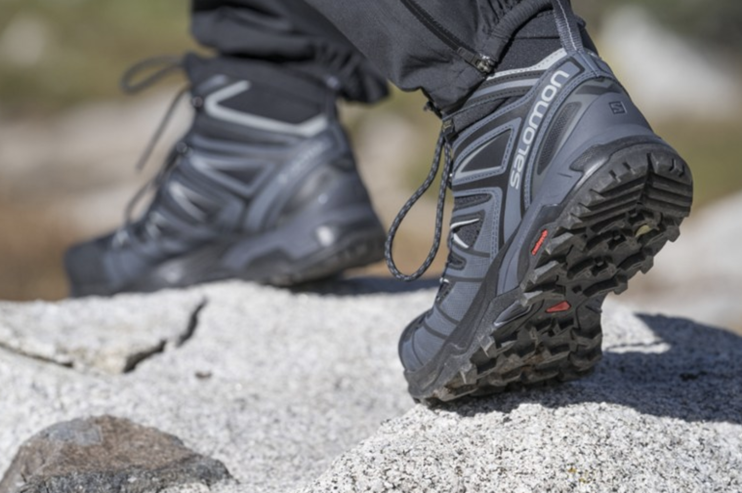 A model wears a pair of Salomon X Ultra 3 Mid GTX Hiking Boots outside
