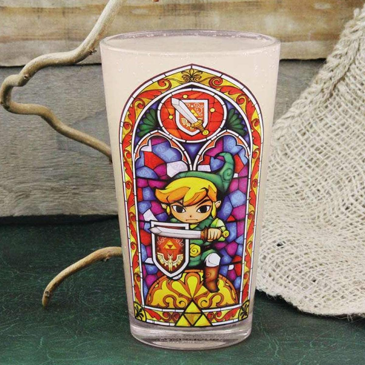 a pint glass with a stain glass style design with toon link on it