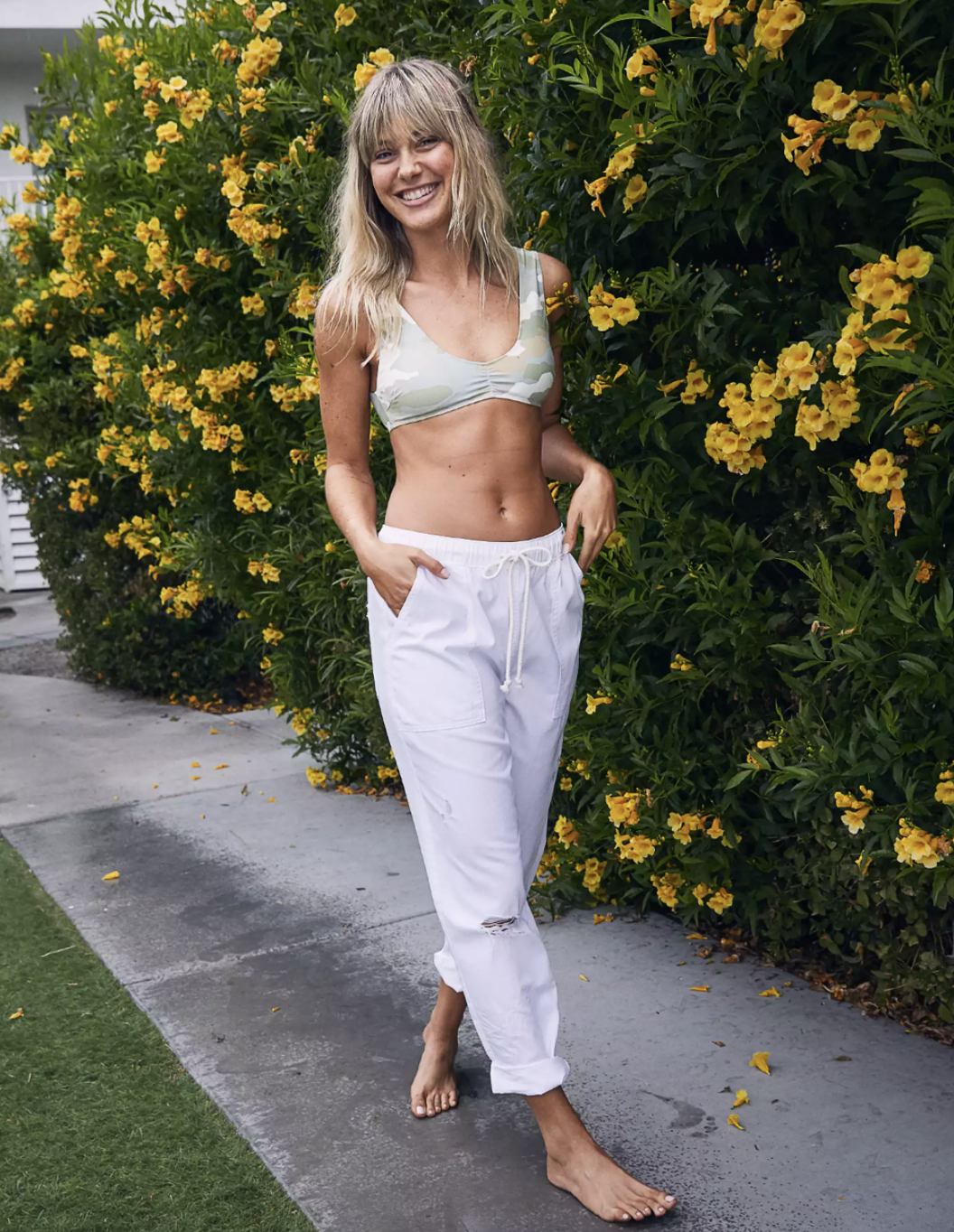 A model wearing the white pants with a bikini top while walking down a sidewalk