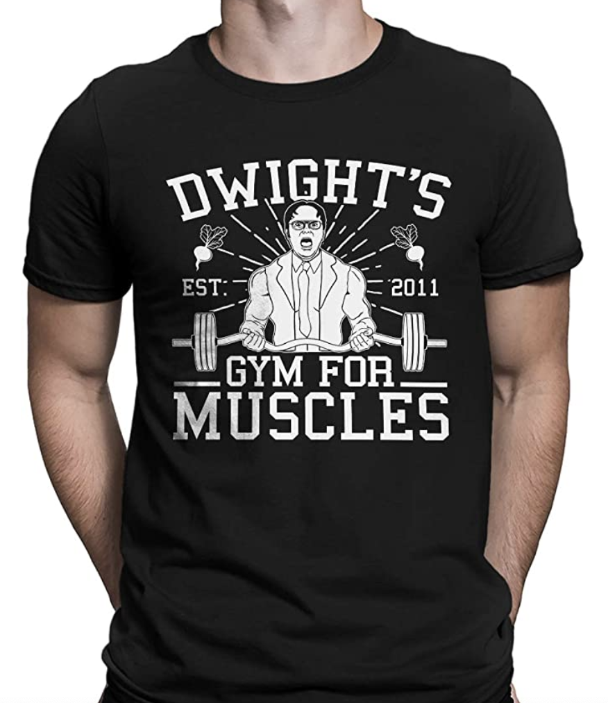 "A model wears a black T-shirt that says ""Dwight's Gym For Muscles"""