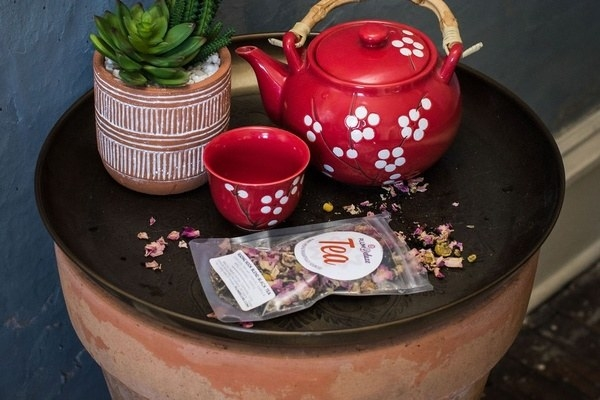 A red teapot and teacup on a coffee table with a bag of loose leaf tea