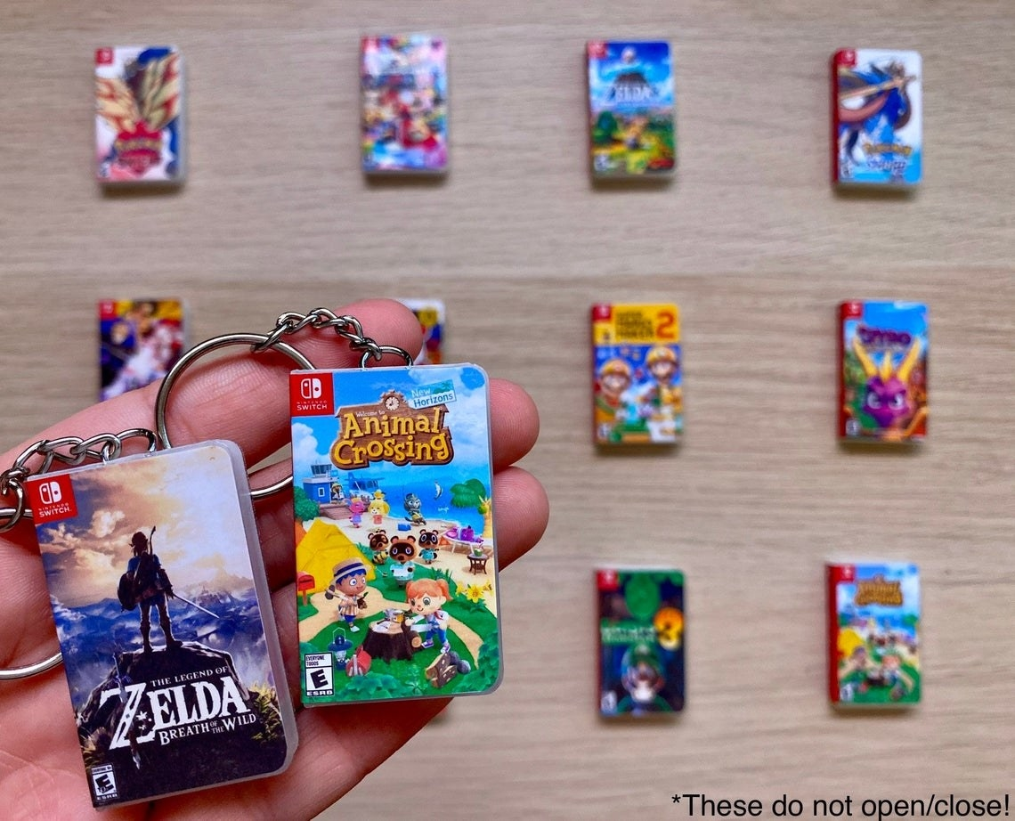 a hand holds keychains that look like tiny nintendo game boxes