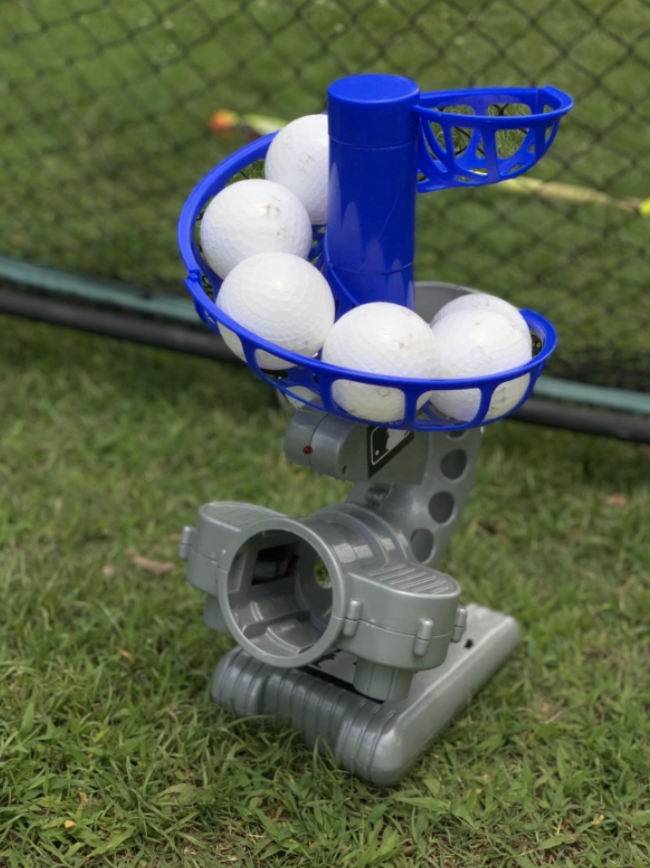 A Franklin Sports MLB Electronic Baseball Pitching Machine in a backyard