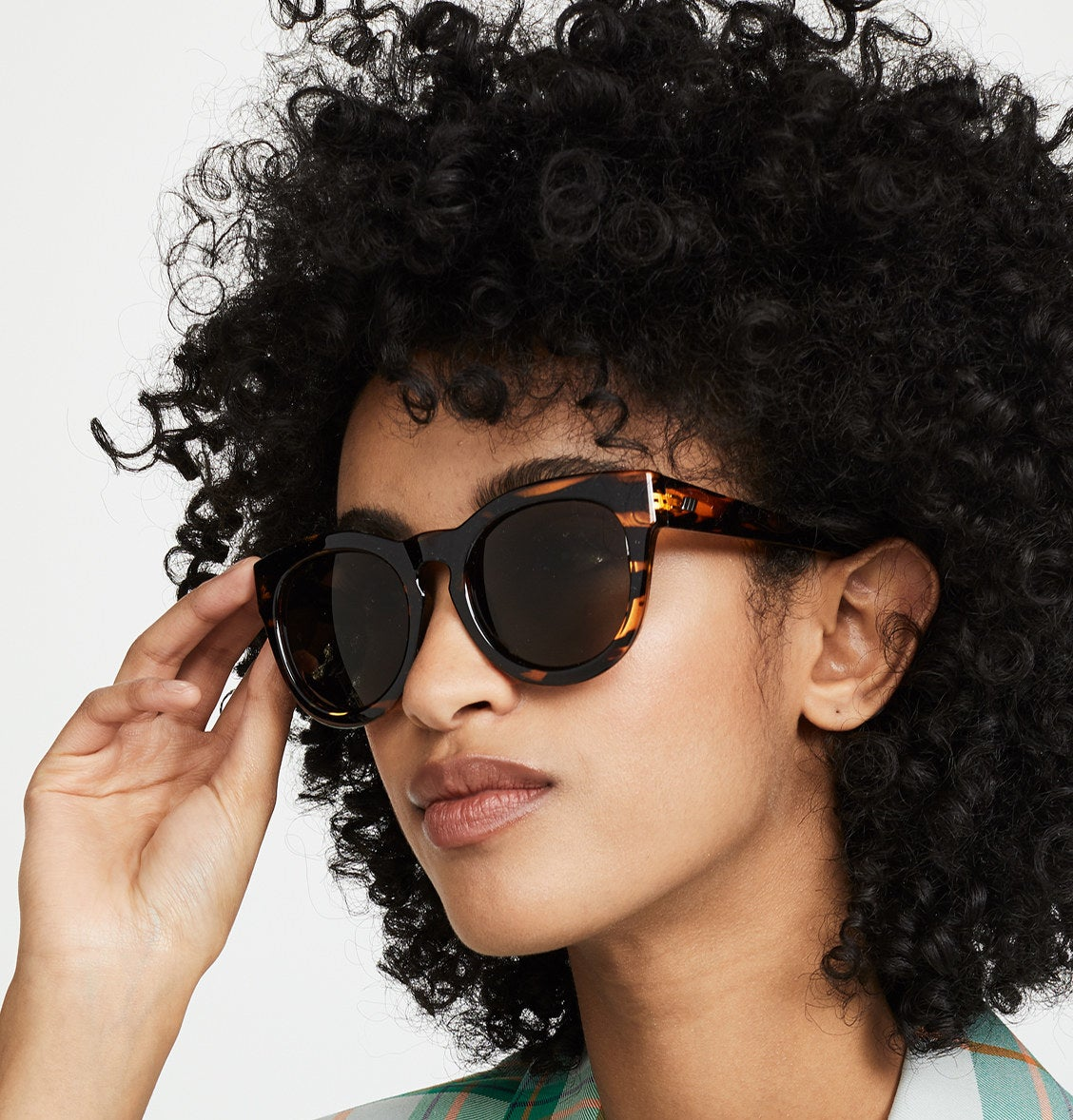 Close-up of model wearing sunglasses with green plaid jacket.