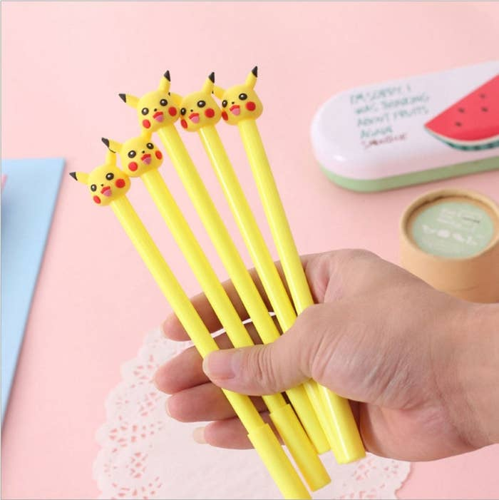 a hand holds a bunch of yellow pens topped with pikachu heads