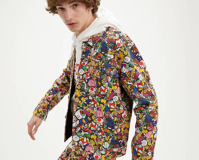 a model wears a jacket covered in nintendo characters