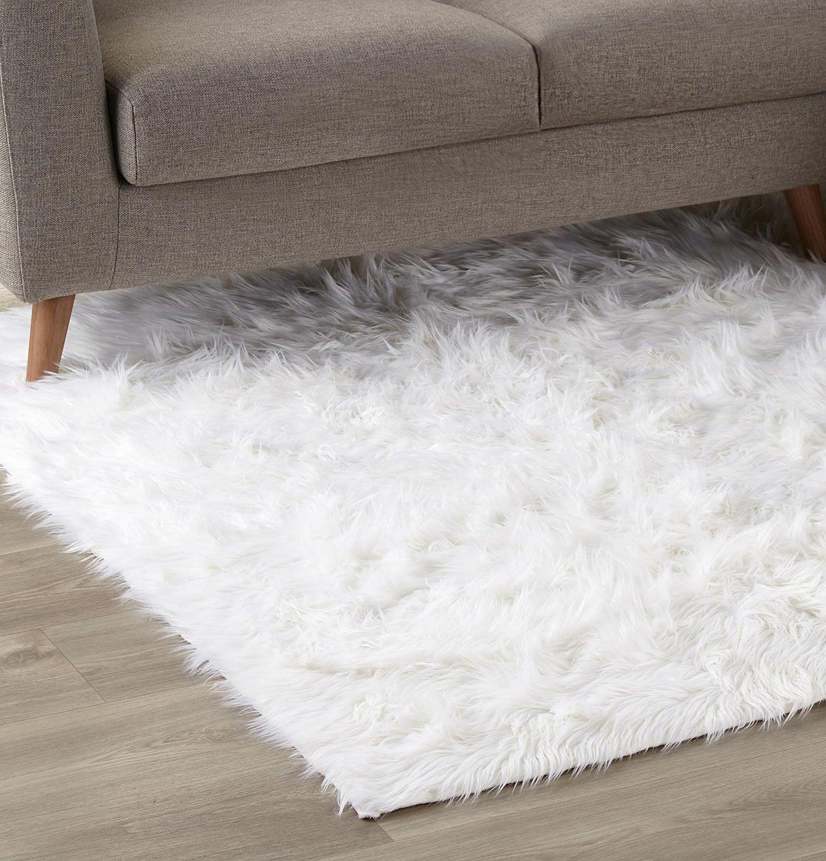A furry rug on the floor near a couch