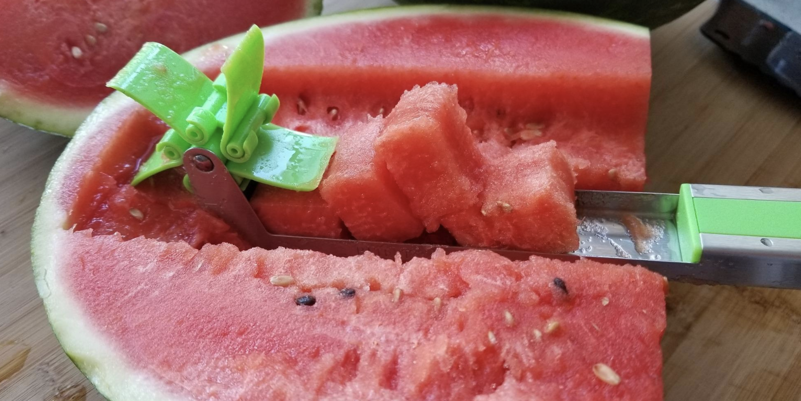 a reviewer pic of stainless steel cutter slicing through watermelon and creating cubes