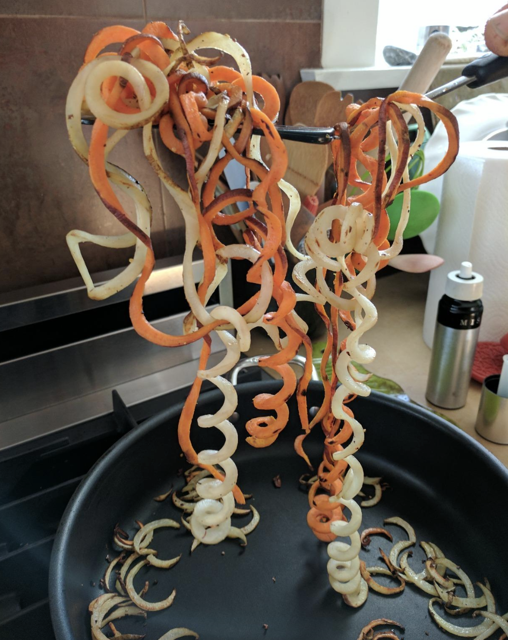 orange and white spiralized veggie noodles being held over pan