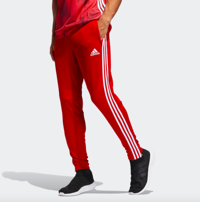 A model wearing the pants, which have an Adidas logo by the pocket and three stripes running down the side