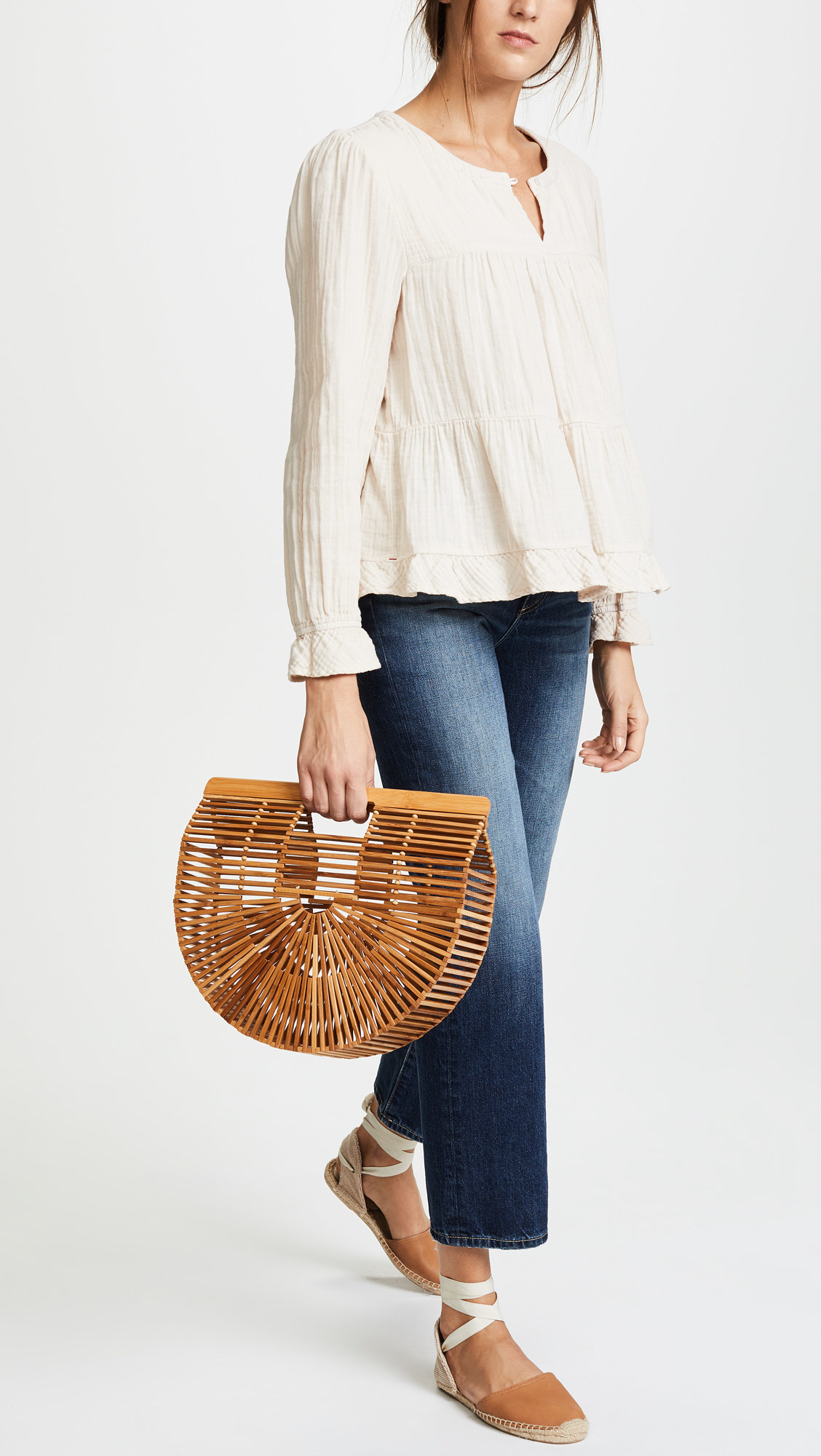 Model holding the curved wood clutch, which is about width of a watermelon