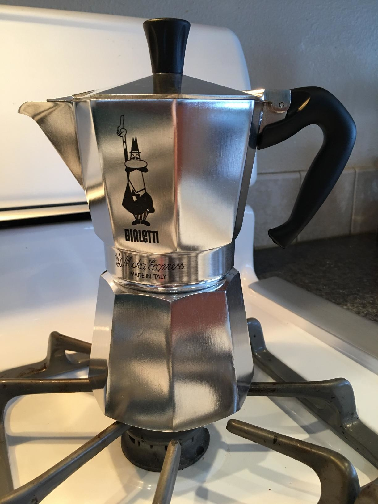A metal Bialetti coffee brewer sitting on a stovetop burner