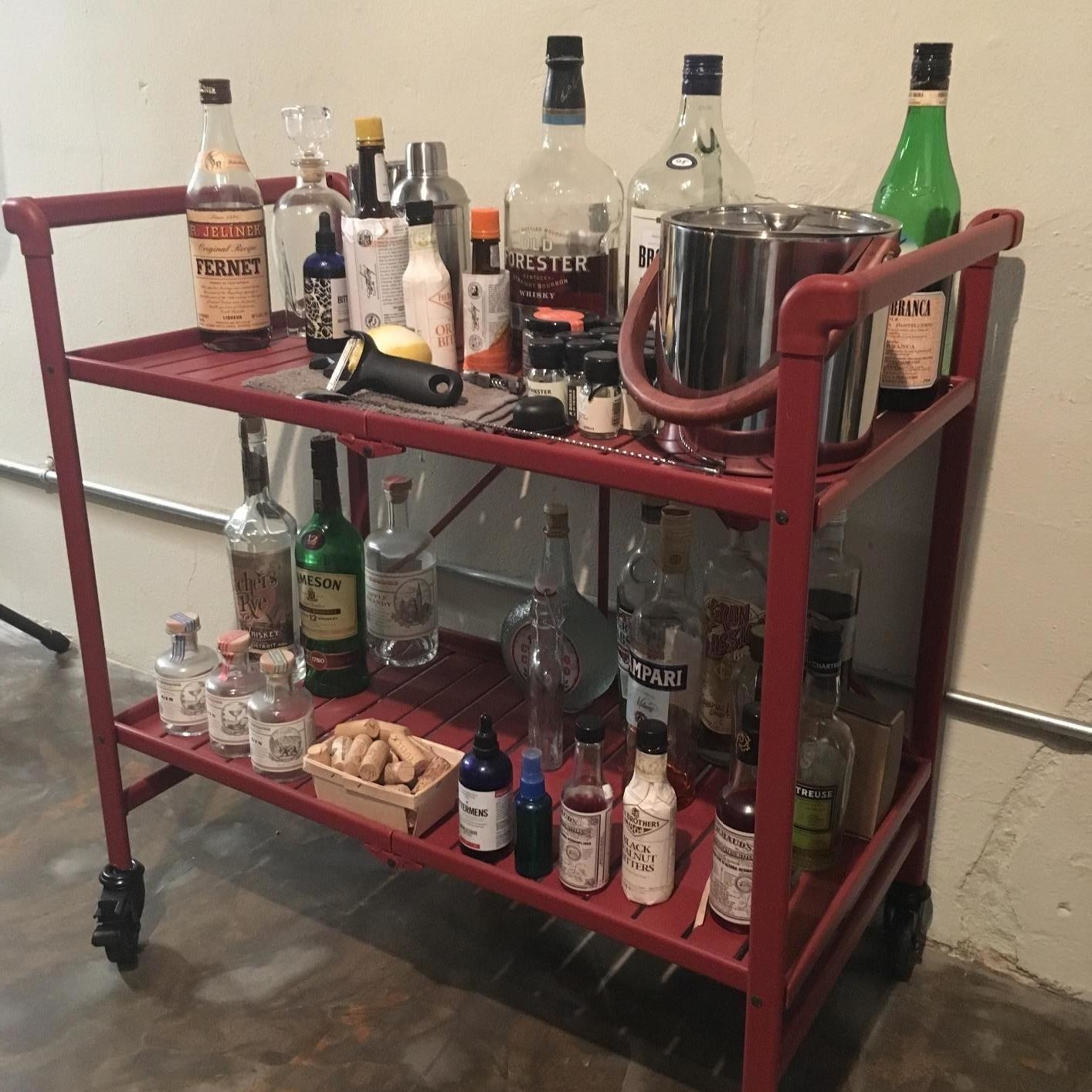 A red, two shelf folding service cart on four caster wheels packed with bottles of booze