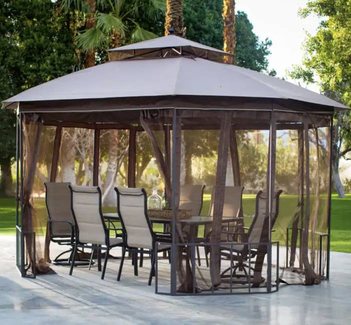 a gazebo top shaped like an octagon with loose, flowing netted curtains hanging down the sides around a set of outdoor furniture